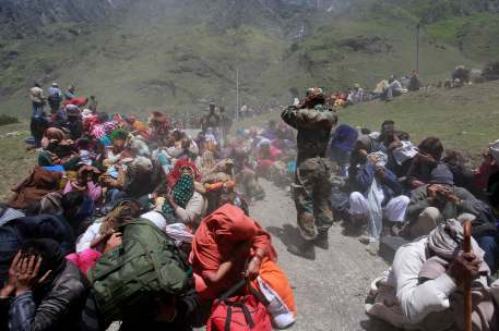 People and soldiers cover their faces as an army helicopter lands during rescue operations at Badrinath in the Himalayan state of Uttarakhand June 21, 2013.