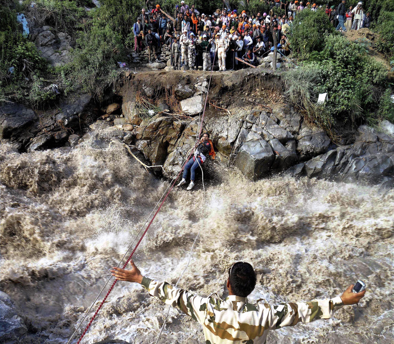 Indo-Tibet Border Police men rescuing stranded pilgrims using a rope at Govindghat in Chamoli district of Uttarakhand on Thursday.