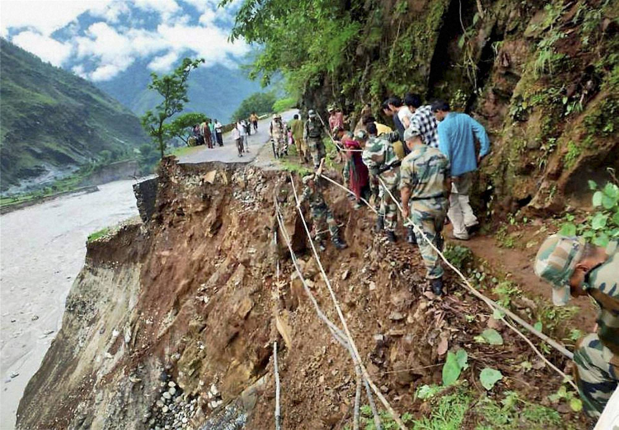 Army personnel carry out rescue work near a washed off road at flood-hit Hemkund in Chamoli district.