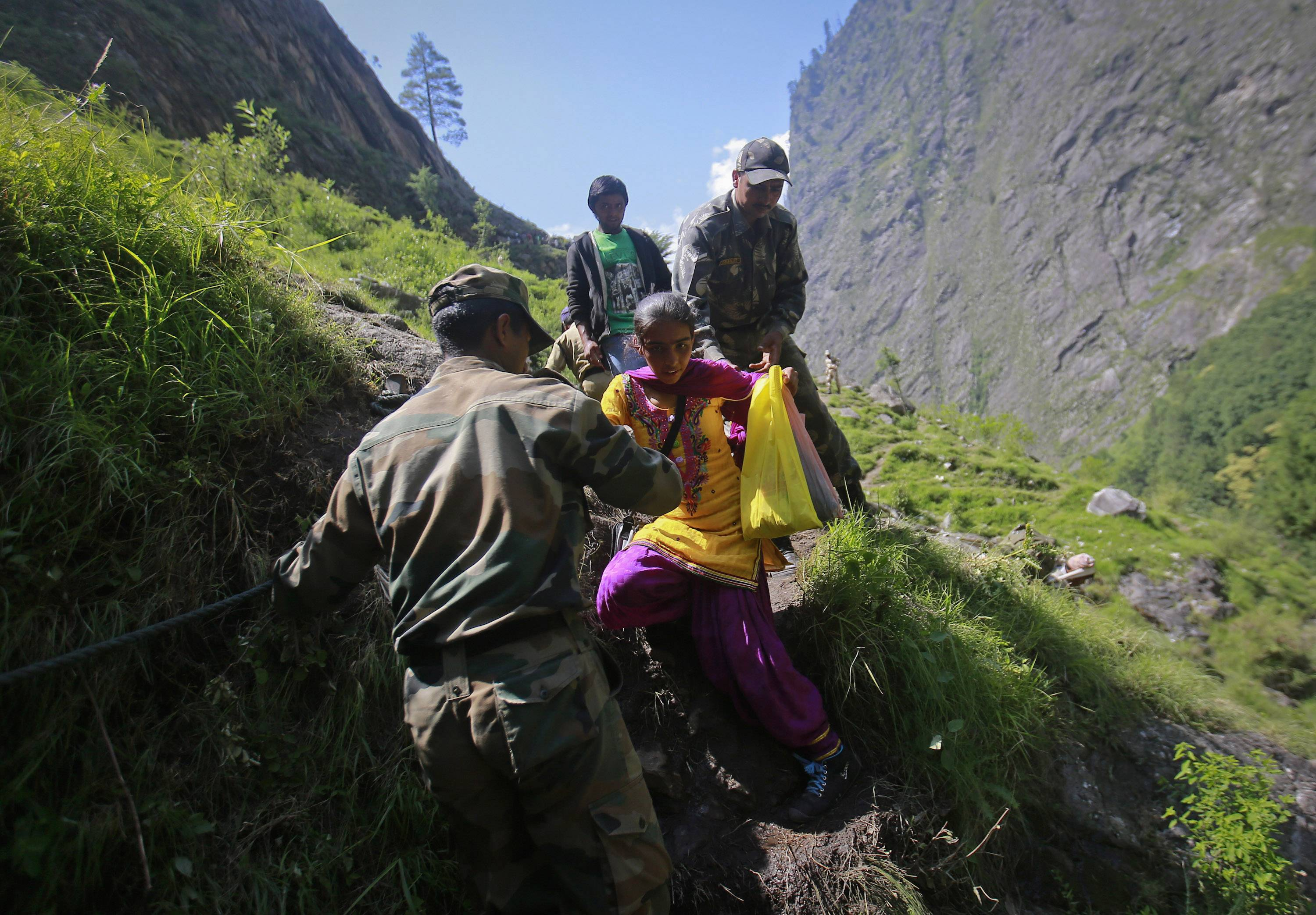 A woman is helped by soldiers to climb down a hill during a rescue operation at Govindghat in the Himalayan state of Uttarakhand June 21, 2013.