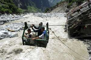 Locals sit in a gondola as they cross the Alaknanda river from Govindghat to the Hemkund Sikh temple following flash floods in Uttarakhand state