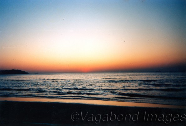 Sun sets in the sea at Miramar beach in Goa