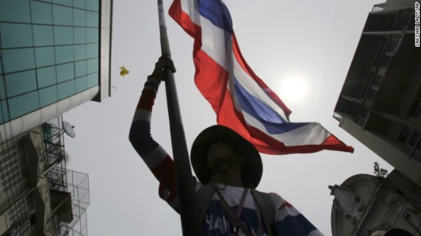 An anti-government protester waves a Thai national flag during a march through streets in Bangkok, Thailand, Monday, May 19, 2014. Thailand's political crisis deepened last week when the Constitutional Court removed Prime Minister Yingluck Shinawatra for nepotism along with nine Cabinet members in a case that many viewed as politically motivated. Protesters say Yingluck's removal is not enough, though. She was simply replaced by Niwattumrong, who was a deputy premier from the ruling party.(AP Photo/Sakchai Lalit)