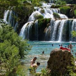 Gente bañándose y refrescándose en el río Krka, con la cascada Skradinski buk de fondo