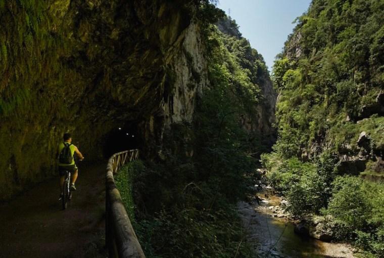 Un clicista llegando a los túneles que atraviesan el desfiladero de Peñas Juntas en la Senda del Oso, Asturias