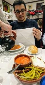 Sirviendo el cocido del puchero individual en Taberna La Bola