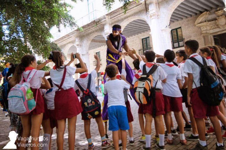 Un grupo de niños viendo la actuación callejera de unos zancudos en La Habana Vieja, Cuba