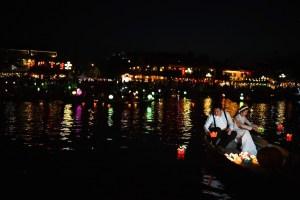 Una pareja de novios en el río Thu Bon iluminado por la noche, Hoi An