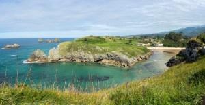 La curiosa forma de la playa de Poo, encajada entre acantilados de la costa asturiana