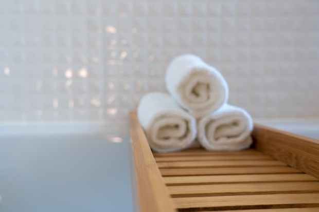 three towels on brown wooden rack