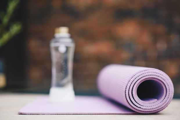 rolled yoga mat and bottle of water in sunlight