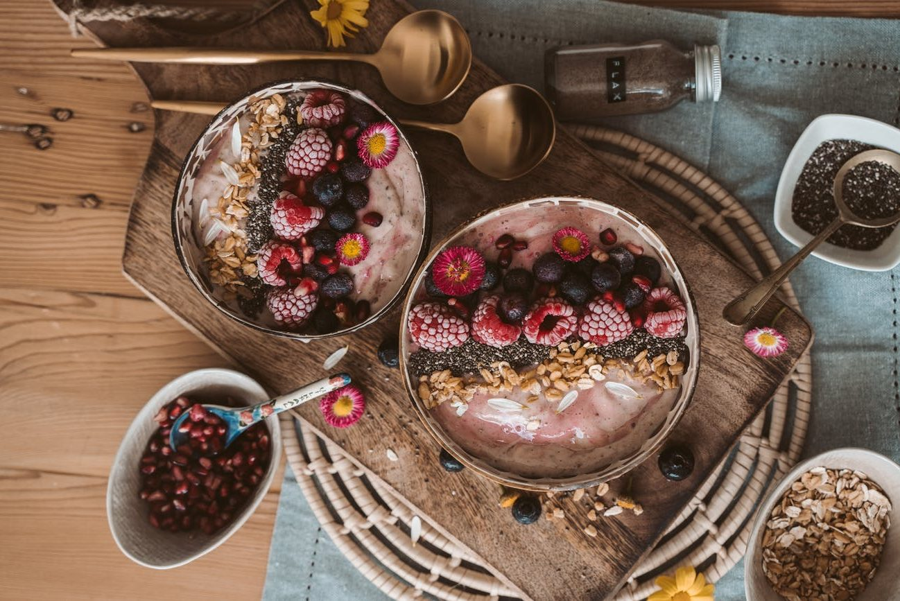 red and white round fruits on brown wooden bowl