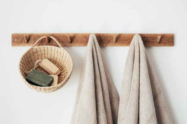 wooden hanger with towels and basket with bathroom products