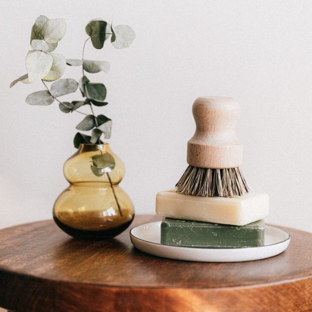 soaps with shaving brush near vase on wooden table