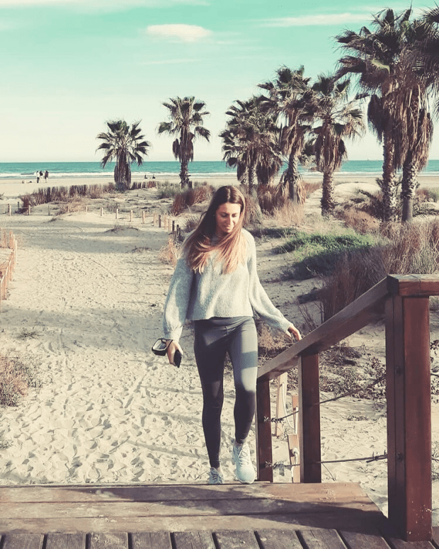 Me, Laura, walking along my local beach in Spain with the Mediterranean sea and palm trees in the background
