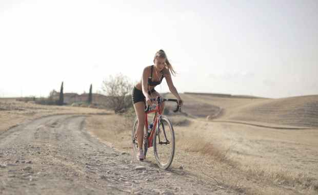 cardio exercise with a girl riding a red bicycle along dirt track