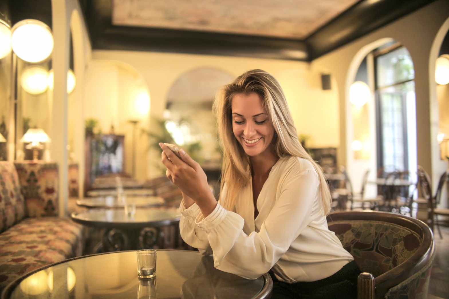 cheerful female having drink in elegant bar