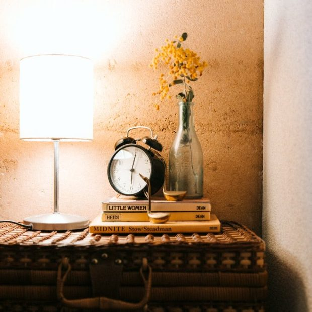 Dimmed bedroom lighting with lamp placed on rustic table with books and deco.