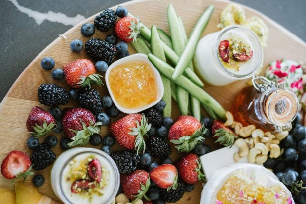 An array of fresh fruit, cucumber, nuts, etc full of vitamins and nutrients for energy