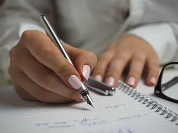 woman in white long sleeved shirt with a baby pink manicure holding a pen writing what to do and what's important on paper
