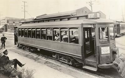 """Streetcar, Richmond (VHS accession number: 2000.186.586.b). This photographic print shows a streetcar parked next to a stop on the Main Street line in Richmond, Virginia. A sign on the front of the streetcar reads """"VA. LEAGUE / BASEBALL / TODAY / ISLAND PARK,"""" and one painted on the streetcar indicates that the fare is six cents. Two women are sitting on the streetcar. A driver and conductor are also on board the streetcar. Two additional conductors, one seated and one standing, are to the left."""