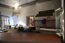 "Installing ""Made in Virginia,"" a collage of objects illustrating Virginia industries of the 20th and 21st centuries. The ship nameboards are on loan from the Mariners' Museum in Newport News, Virginia."