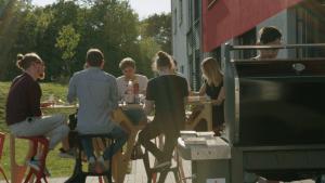 Das Vaira-Team sitzt draußen um einen Tisch versammelt und isst. Im Vordergrund wird ein großer BBQ-Grill bedient.