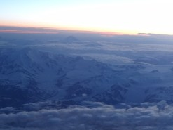 Flug Tokio - New York, hoch ueber Alaska; Es war tief in der Nacht, doch die Mitternachtssonne vermochte ueber den Nordpol zu scheinen. Der hohe Berg im Hintergrund ist hoechstwahrscheinlich Mound Denali /McKinley, der hoechste Punkt Nordamerikas