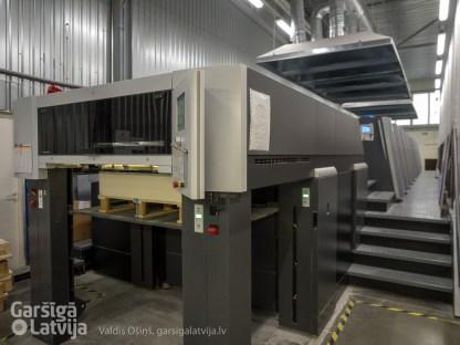 Heidelberg Speedmaster 10 sekciju UV mašīna ar vienlaicīgu abpusējo druku, kuras krāsa nožūst iznākot no mašīnas.