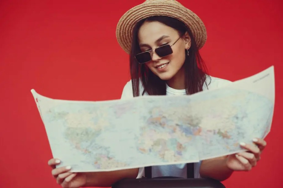 happy young lady studying map on red background