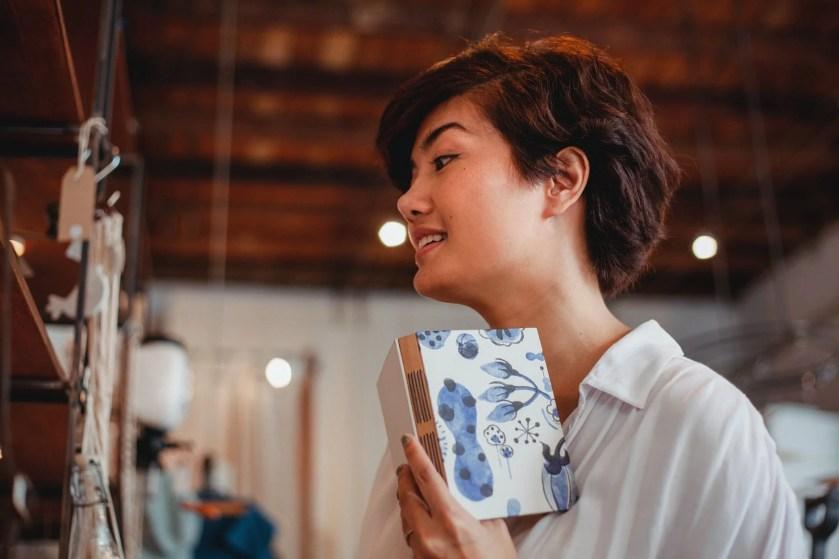 joyful young ethnic lady choosing goods in creative souvenir boutique