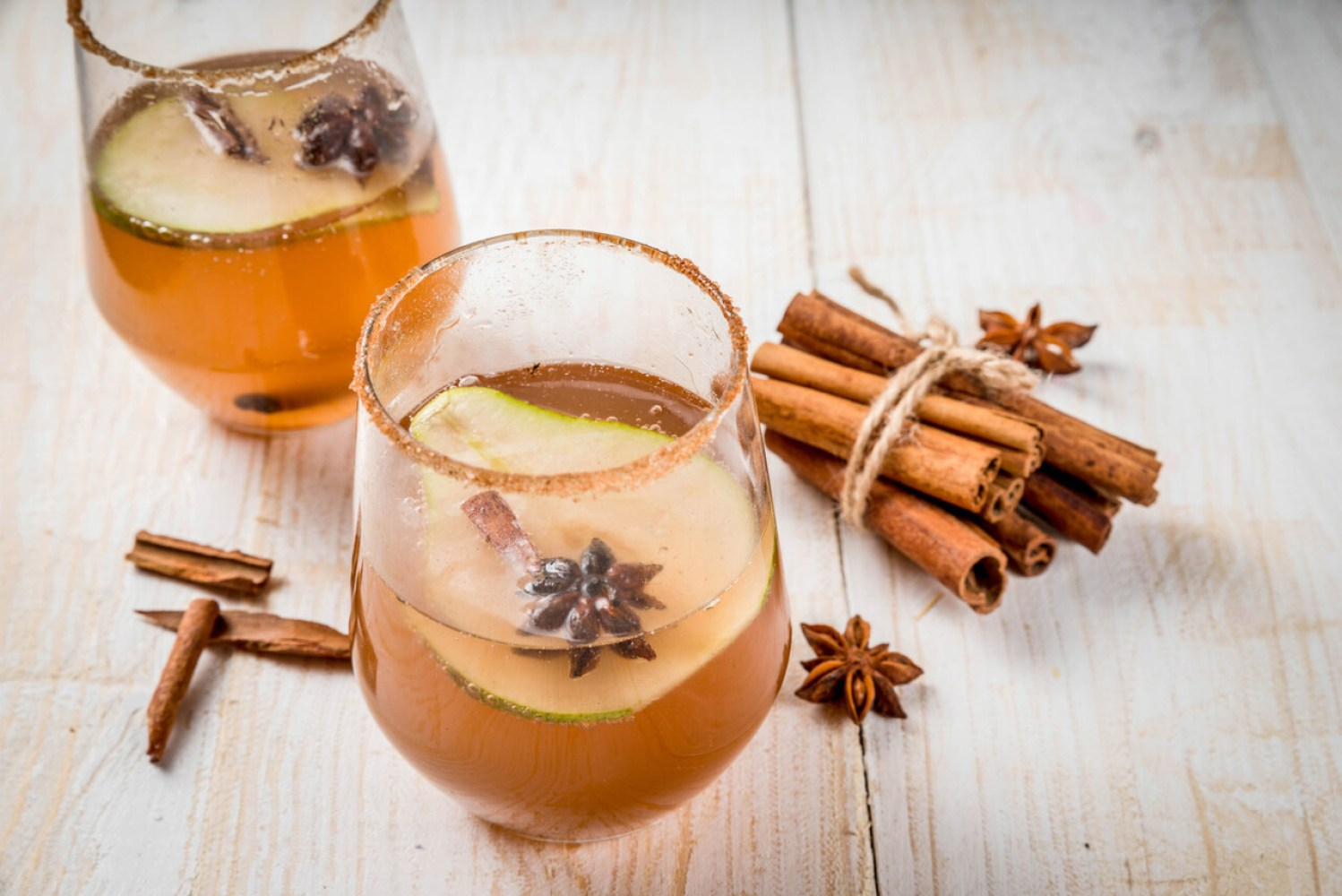 Autumn drinks. Mulled wine. Traditional autumn spicy cocktail with pear, cider and chocolate syrup, with cinnamon, anise, brown sugar. On a white wooden table. Copy space