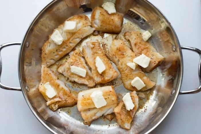 Cod seasoned and topped with butter in a skillet.