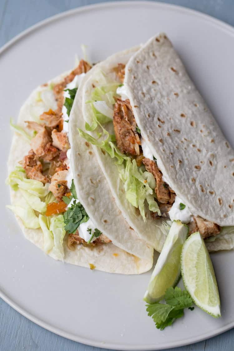 Slow cooker chicken fajitas in a burritos on a plate with limes.