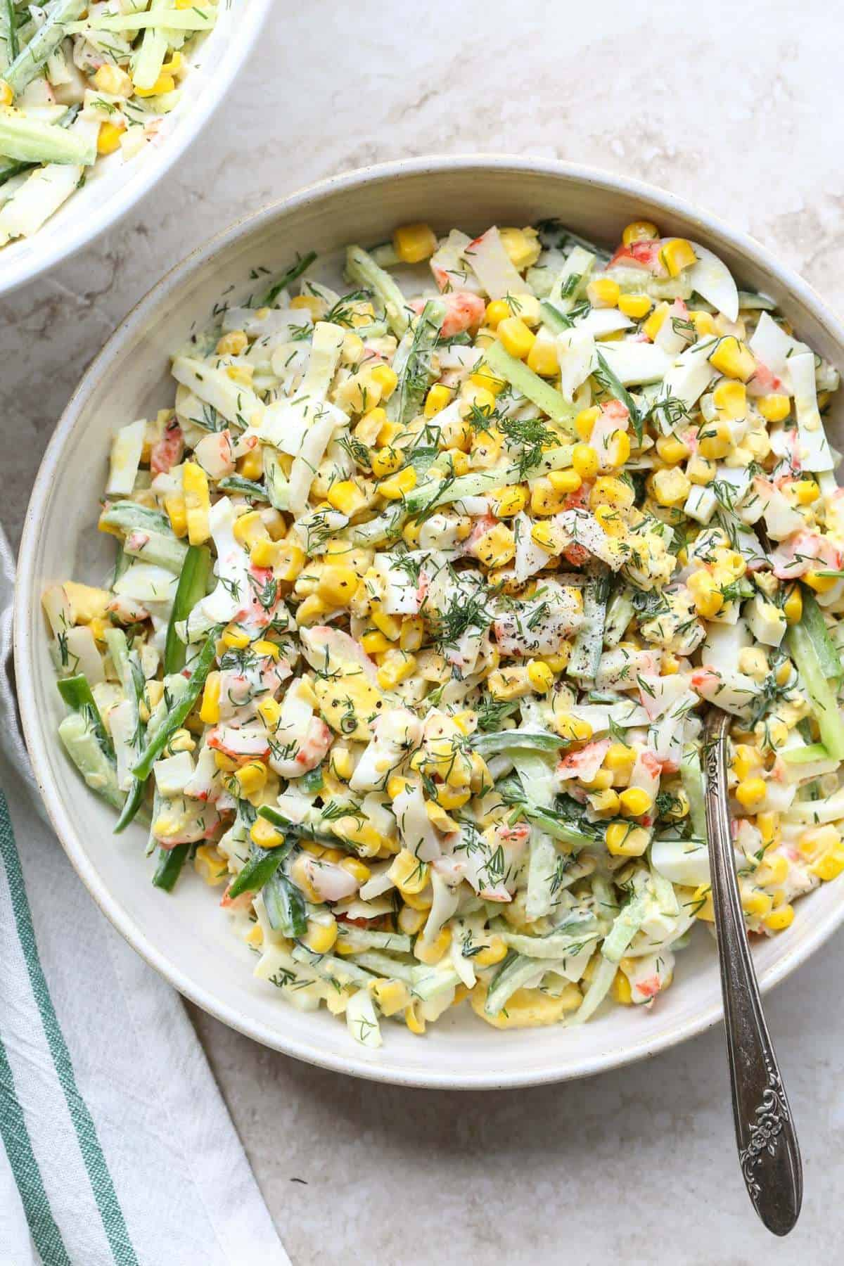 Crab corn egg salad recipe with a mayo dressing, topped with dill.