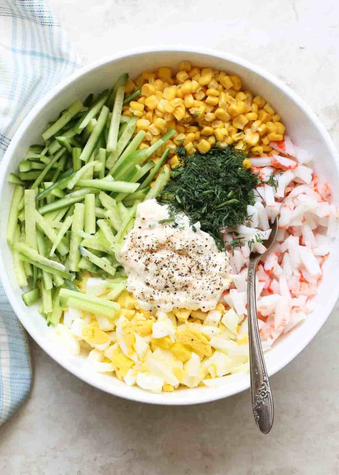 Ingredients cut for Egg salad in a bowl with mayo and dill.