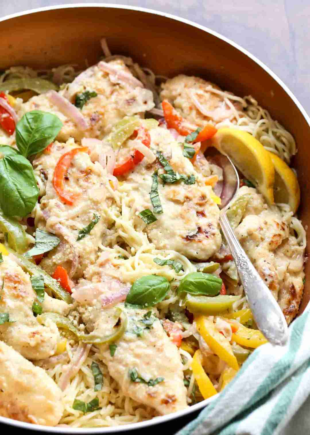 Angel hair pasta in a skillet with chicken and vegetable garnished with fresh lemons.