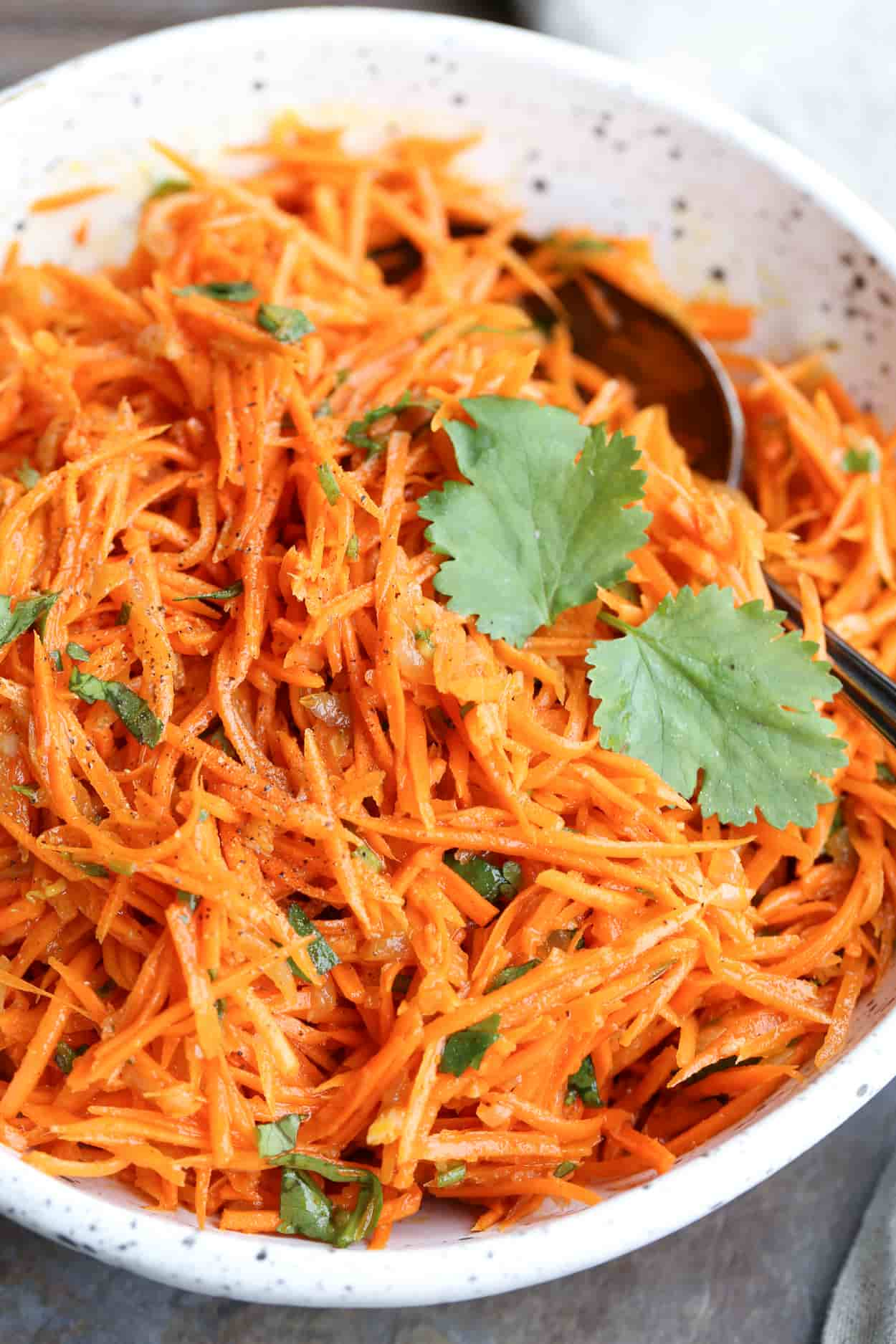Korean carrot salad recipe in a bwol with fresh chopped herbs and a spoon.