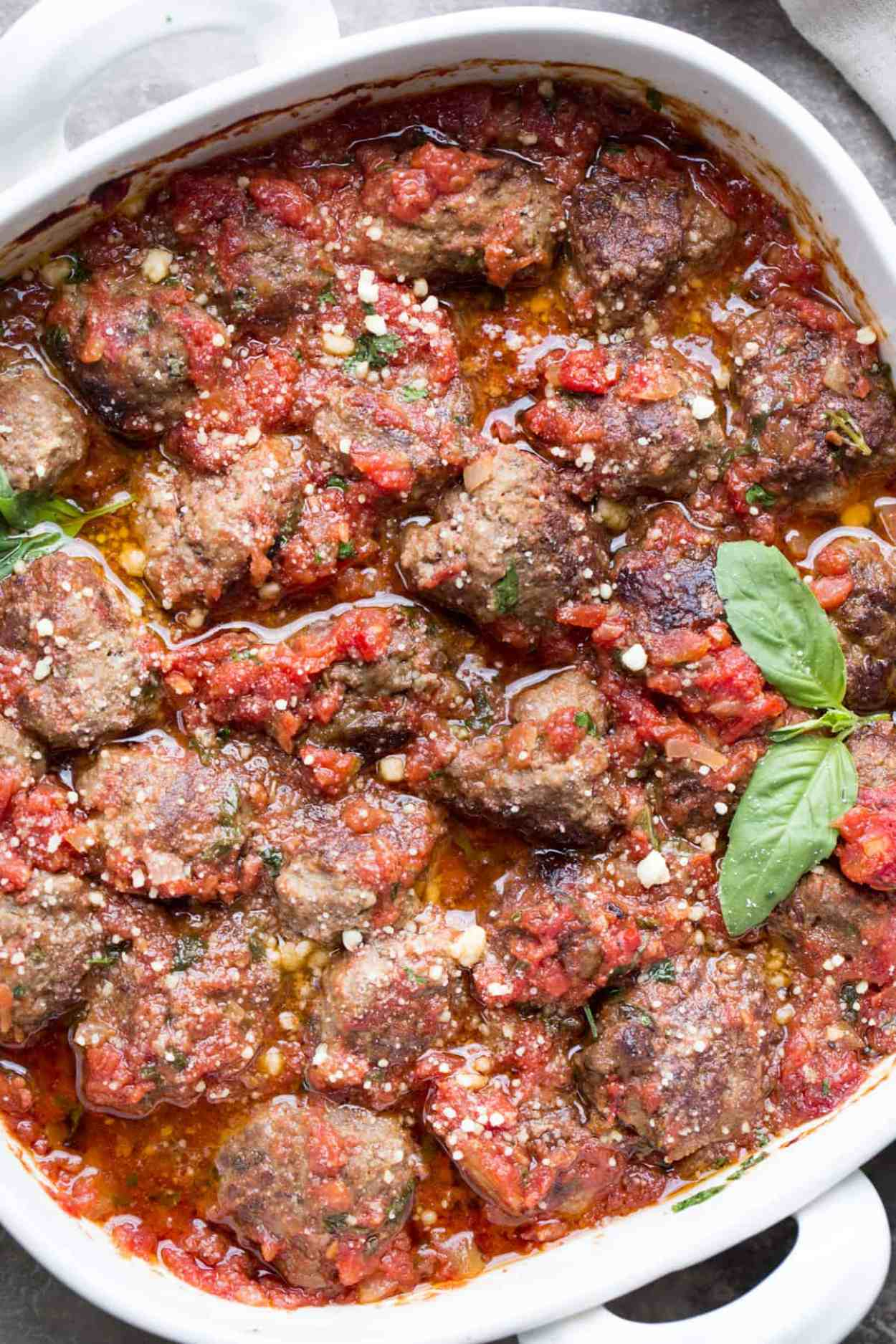 Easy meatball recipe in a casserole dish topped with Parmesan cheese, and fresh basil.