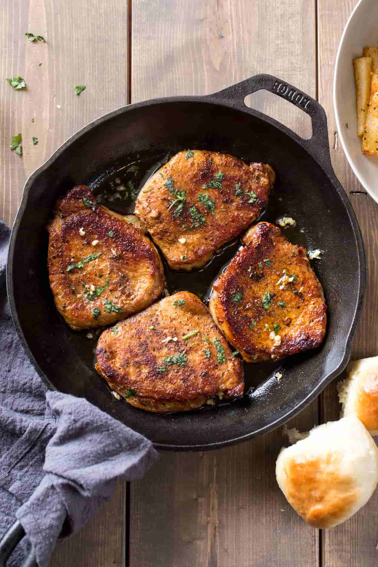 Pork chops in a skillet topped with garlic and greens. Next to dinner rolls.