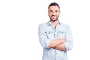 Smiling man standing in front of white background arms crossed