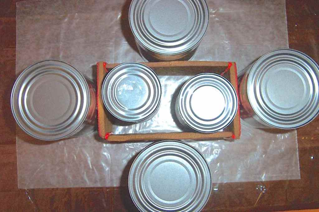 Showing aluminum cans holding the glued sides of box in place for drying.