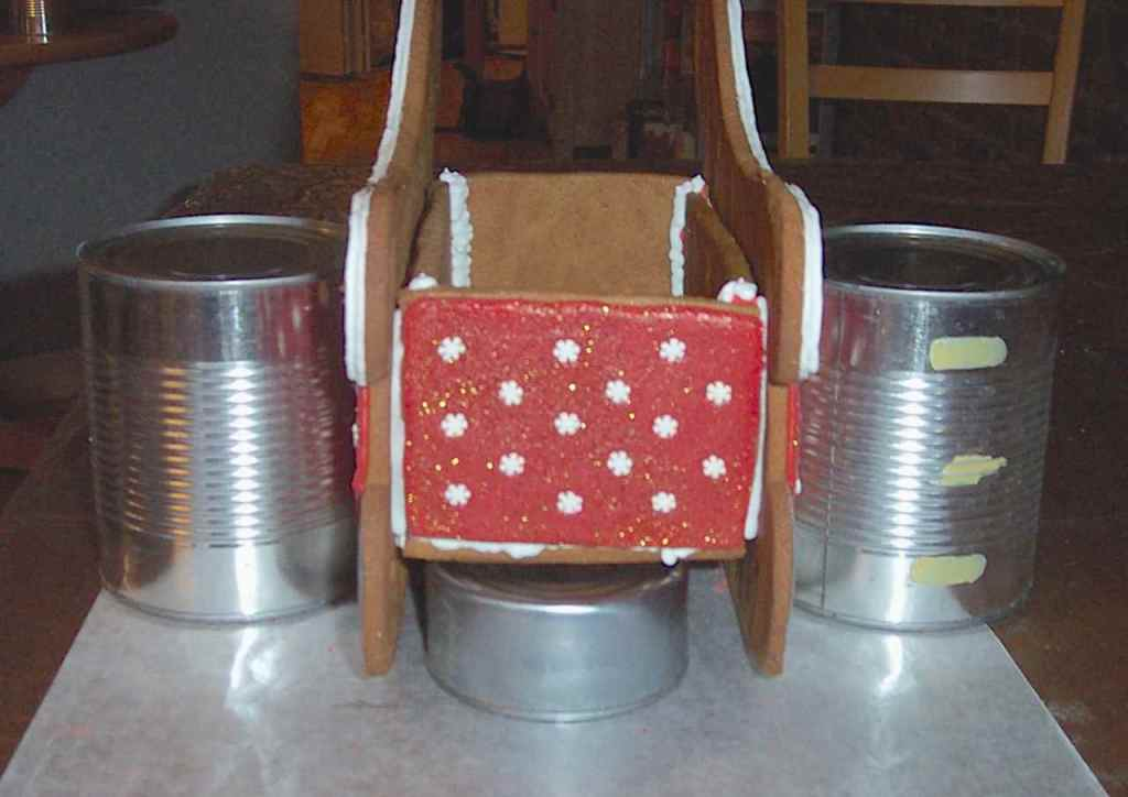 Front view of sleigh with box glued in and supported by cans while drying. A tuna can holds up the box on the bottom.