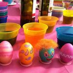 Easter egg decorating table with colored eggs, decorating supplies and wine.