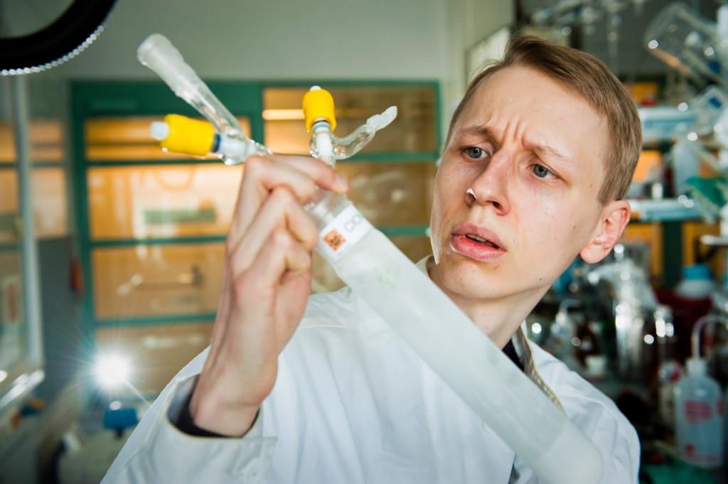 Teemu Arppe tarkastelee laboratoriossa kylmäsormea, johon on jäädytetty kloorisyaania.