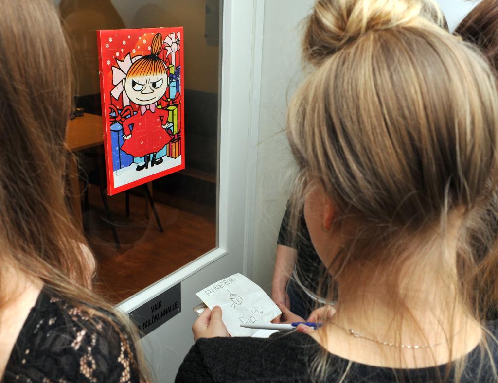 Suljetussa ovessa Pikku Myy -joulukalenteri, jonka ympärille pelaajat ovat kerääntyneet miettimään yhdisteen rakennetta.