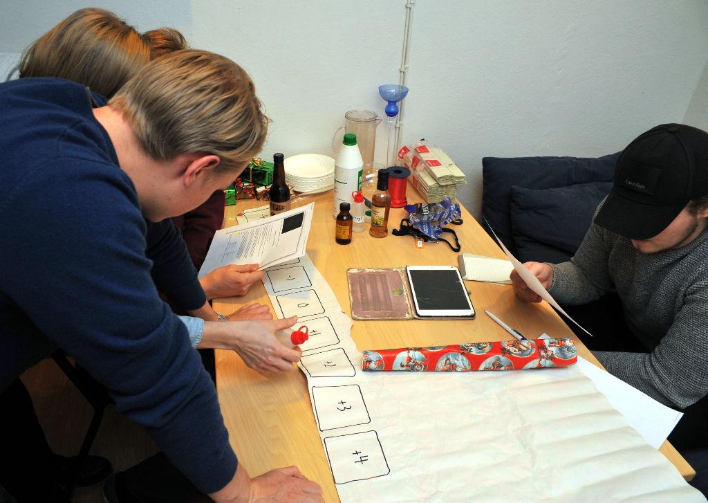 Pelaajia tutkimassa pöydällä olevia papereita ja pulloja.