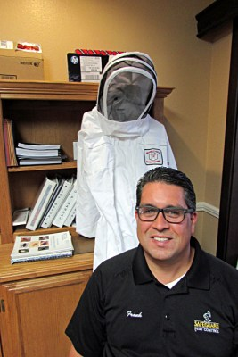 Frank Martinez, Safeguard's general manager, said every company truck has a bee suitbecause technicians encounter bees every day. (VBR)