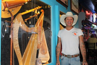 Brady Buntin, a self-described history nerd, stands by more than 40 wooden instruments he makes. (VBR)