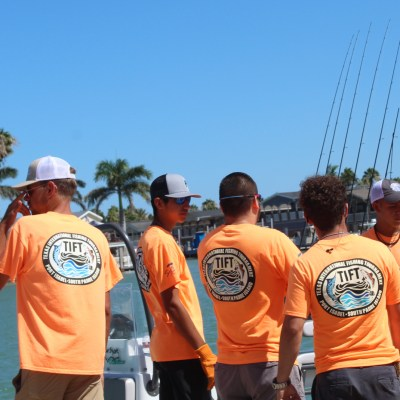 TIFT volunteers wait for fishing boats to arrive at the dock at the Port Isabel Marina.